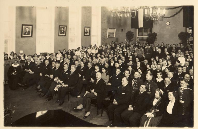 Skolas zāle pilna ar cilvēkiem uzvalkos, tautastērpos un armijas uniformās