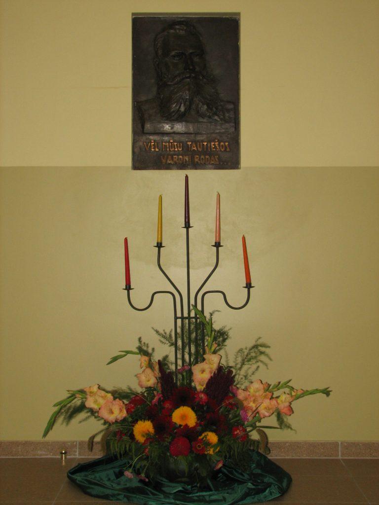 Andreja Pumpura bareljefs ar ziedu kompozīciju un svečturi