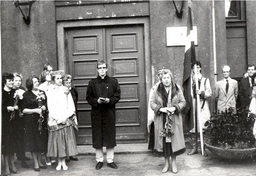 Skolas ieejas durvis ar atjaunoto nosaukuma plāksni. Priekšplānā direktore Anna Zommere, luterāņu mācītājs un vairākas skolotājas