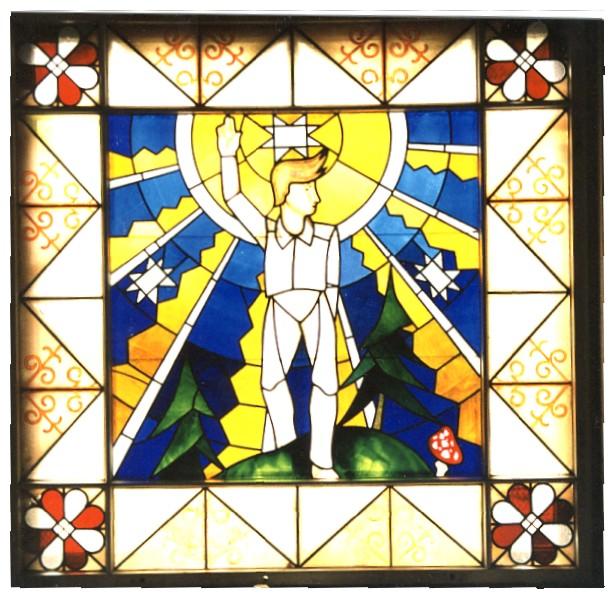 """Vitrāža """"Uz skolu"""" -  austošas saules apspīdēts zēns ar sveicienā paceltu roku."""