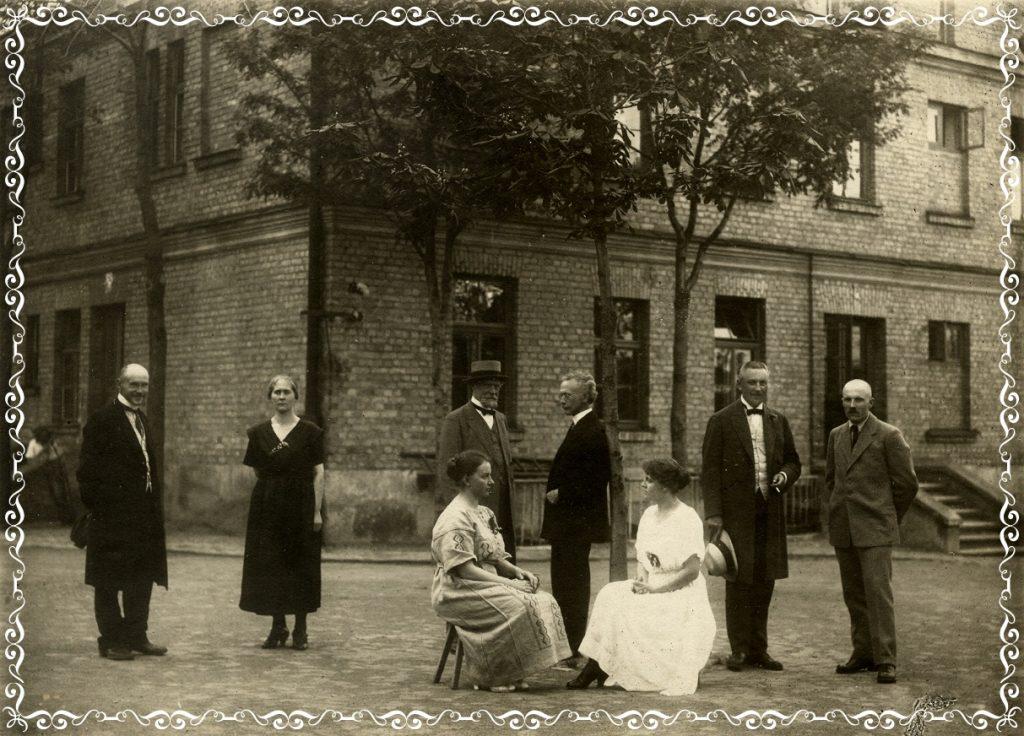 Skola un skolotāji 1921. gadā. Divstāvu ķieģeļu ēkas priekšā redzami 8 skolotāji - 5 vīrieši un 3 sievietes.