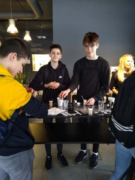 Divi puiši pie galda ar kosmētikas produktu izejvielām