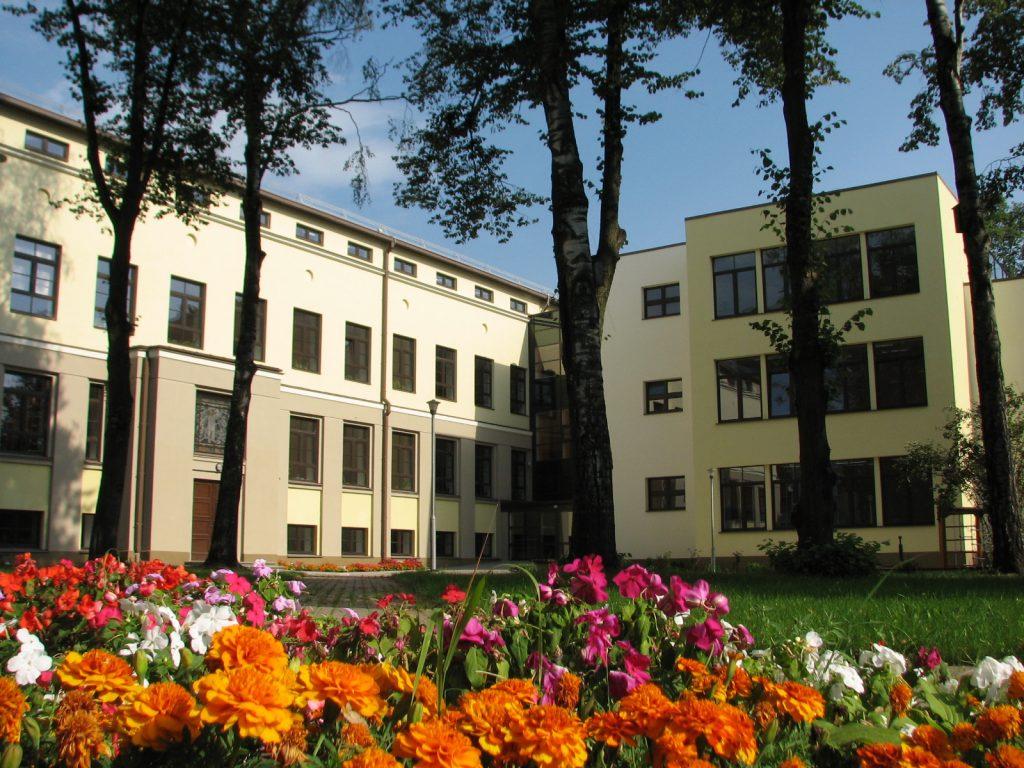 kolas ēka ar puķu dobi pagalmā